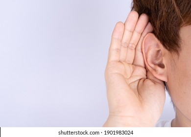 man hearing loss or hard of hearing and cupping his hand behind his ear isolate grey background, Deaf concept.