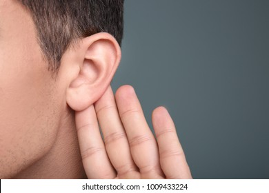 Man with hearing problem on grey background, closeup