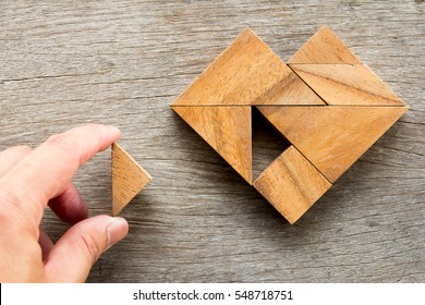 Man held piece of tangram puzzle to fulfill the heart shape on wooden table (Concept of love)