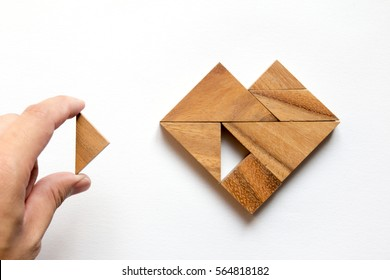 Man held piece of tangram puzzle to fulfill the heart shape on white background (Concept of love)