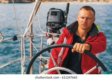 Man at the helm on a sailing yacht in sea.