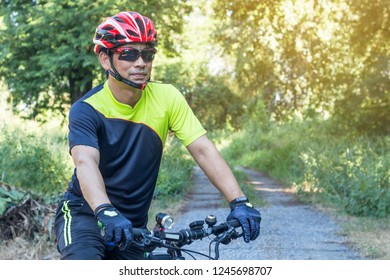 Man with helmet glove for safety riding a bicycle at countryside road along a forest,Cross country riding,cycling activity and sports.