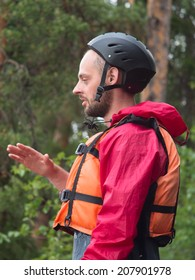A man in a helmet and life jacket closeup on a background of forest