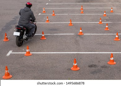 Man in helmet on motor-cycle making exercises on car-park among orange traffic cones