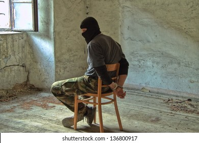 Man with helmet sitting in a room with handcuffs on her hands