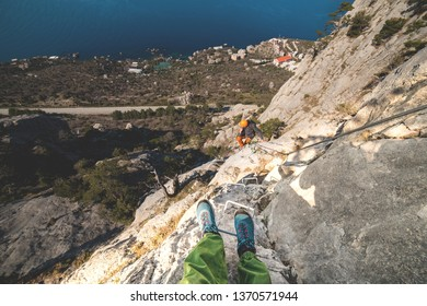 Man in helmet and special equipment moving along via ferrata in the mountains near the sea in sunny day.  And photografer's boots are in the shot because of wide angle lens..