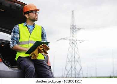 A man in a helmet and uniform, an electrician in the field. Professional electrician engineer inspects power lines work.