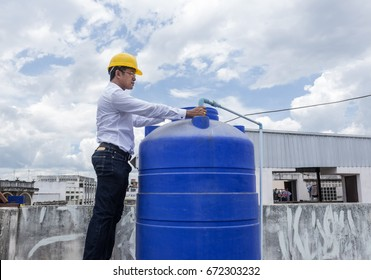 Man with helmet work  with water tank.