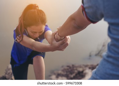 Man help hand giving outstretched for salvation to climbing girl, believe support to companions business for strength team,believe in god help team, business work concept.