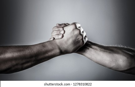 Man help hands, guardianship, protection. Handshake, arms. Friendly handshake, friends greeting. Rescue, helping hand. Two hands, helping hand of a friend. Black and white.