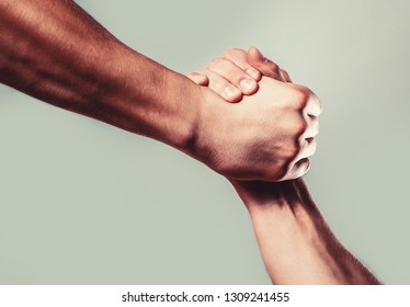 Man help hands, guardianship, protection. Two hands, isolated arm, helping hand of a friend. Friendly handshake, friends greeting. Rescue, helping hand. Male hand united in handshake.