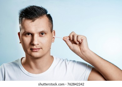 The man with the help of a hygienic cotton swab is reading his ear. The concept of body hygiene.