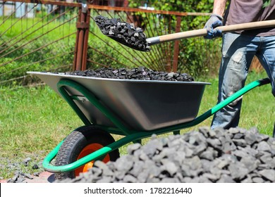 Man with the help of shovel loading crushed stones in the wheelbarrow. Laying the foundation, building project