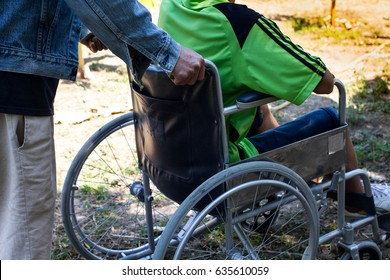 Man helping disabled guy on wheelchair in the garden with sunset