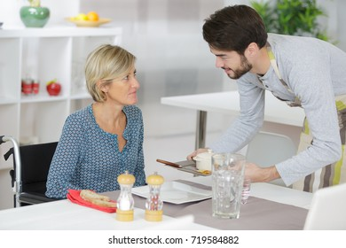 man helping disabled woman with her meal