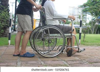 Man helping disabled woman on wheelchair in the park