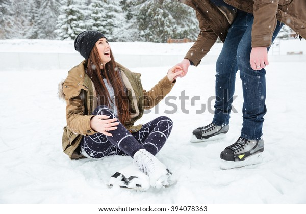 Man helping girl to stand on the ice rink outdoors