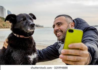 Man helping his grumpy dog firend to take a social media selfie image using a smartphone