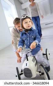 Man helping little boy on a retro toy car