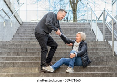 Man helping senior woman to get up while she is sitting on stairs outdoors in the city, holding her knee