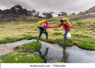 man helping woman over a stream in the Andes in Peru on the way to base camp during a mountaineering expedition