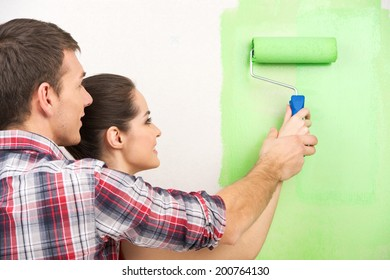 man helping woman paint wall. beautiful couple holding painting roller together