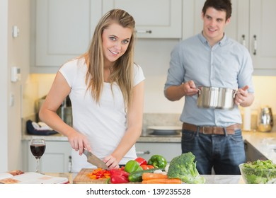 Man helping woman  prepare the meal in kitchen