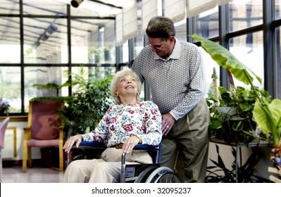 man helping woman in wheelchair