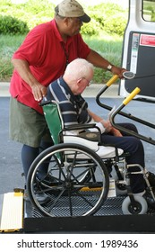 A man helps another into a wheelchair equipped van.