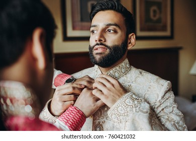 Man helps bearded indian groom to put his rich wedding clothes