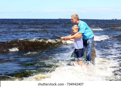 Man helps a boy with fishing road in hands pull out a caught fish among stormy waves - father and son sea fishing