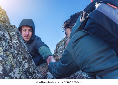 A man helps his friend to climb to the top. Hiker gives a hand to pull up the on mountain.