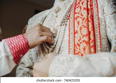 Man helps indian groom to put his rich wedding clothes with pearls