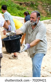 Man helps pass along a bucket of dirt to a fellow missionary on a trip to build a church in Jamaica.
