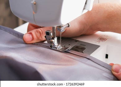 A man hem a curtain on sewing machine. Sewing, hobbies, hobby, home improvement. - Shutterstock ID 1726392469