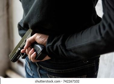 Man hide gun behind their back