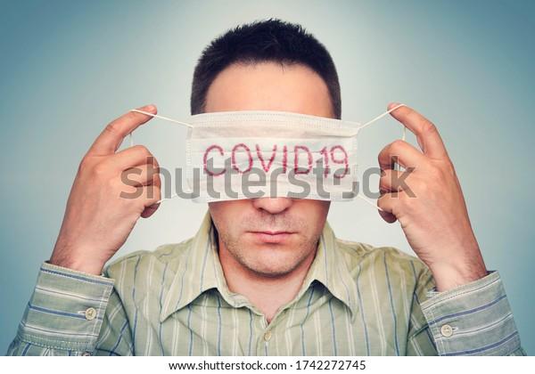 El hombre esconde los ojos detrás de una máscara médica marcada Corvette. El concepto de fatiga por cuarentena global y autoaislamiento. Usando una máscara facial
