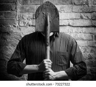 A man hides his face behind a shovel. Depersonalization, a metaphor.