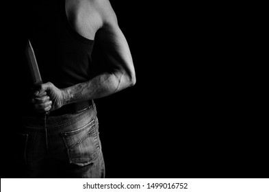 A man hides a knife behind his back in black and white.