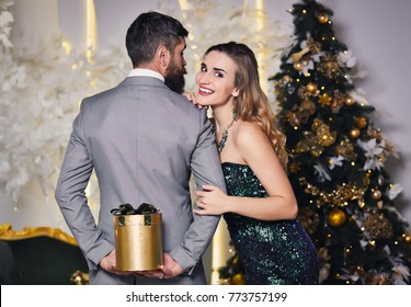 Man hides the present behind the back from his pretty girlfriend. Guy hiding Christmas gift behind his back. Woman wondering of gift. Newlyweds celebrate the new year or special occasion concept.