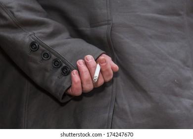 man hiding cigarette behind back