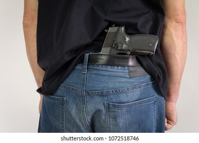 Man hiding the gun behind his back.Illegal possession of weapons