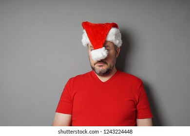 man hiding his face behind santa claus hat - christmas hater or holiday depression concept
