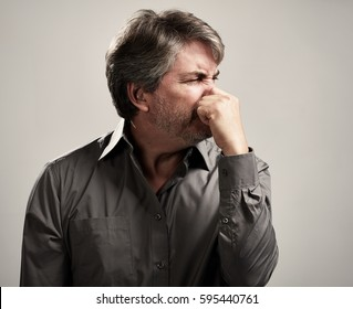 Man hiding his nose