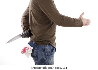 man hiding a knife behind his back while offers a handshake