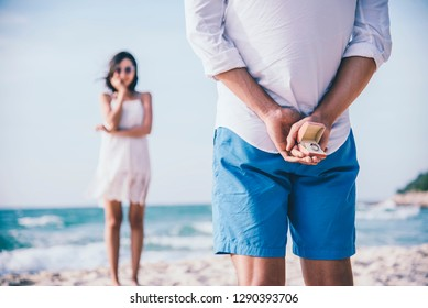 Man hiding a ring behind for making surprise proposal to his girlfriend at the beach. Love and marriage concept.