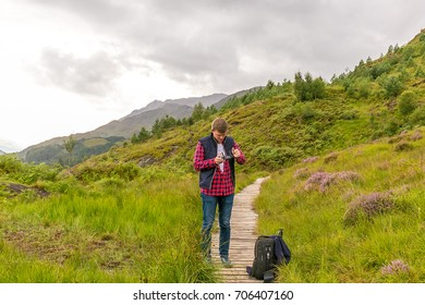 Man in Highlands mountains in Scotland, UK
