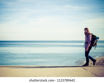 Man hiker backpacker walking with backpack by seaside at sunny day. Adventure, summer, tourism active lifestyle. Young long haired guy tramping