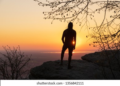 Man hiker in black tracksuit standing on mountain cliff in sunset looking to vew over the small town Vrsac in Serbia after long hike.