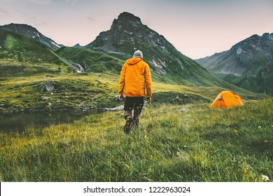 Man hiker and his camping tent in mountains Travel adventure healthy lifestyle active summer vacations outdoor in wilderness